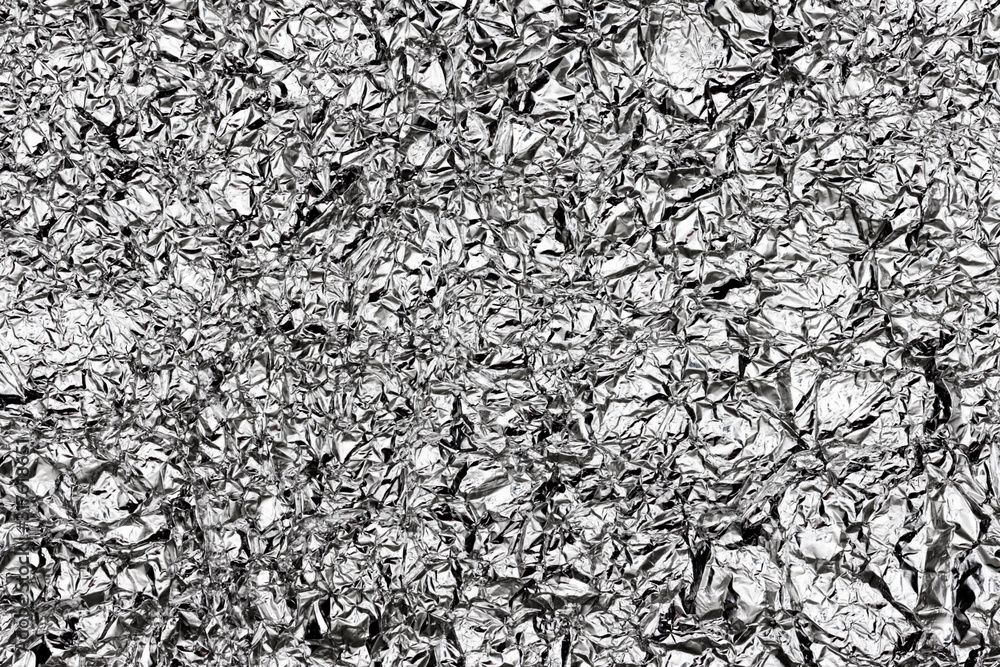 Fototapeta Texture on the cooled down surface of melted tin. Surface of a liquid metal alloy made of steel with impurities. Shiny sheet of aluminum foil, closeup. A sheet of decorative paper with silver coating.