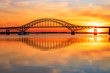 canvas print picture -  Steel tied arch bridge spanning a bay with crystal clear reflections in the water at sunset. Fire Island Inlet Bridge, part of the Robert Moses Causeway on Long Island New York.