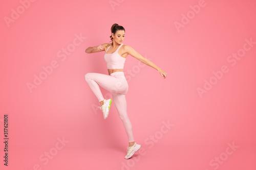 Sporty woman exercising in studio. Tablou Canvas