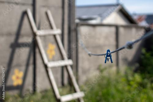 Fototapeta escalera apoyada en muro con cordel azúl en tendedero de ropa