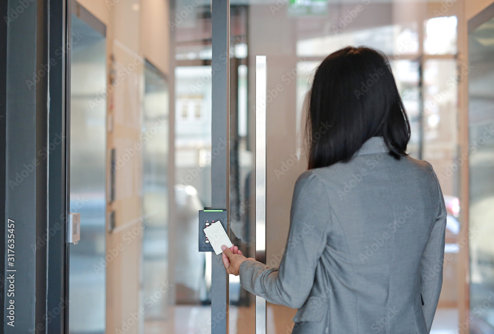 Fototapeta Young officer woman holding a key card to lock and unlock door for access entry. Door access control. Back view.