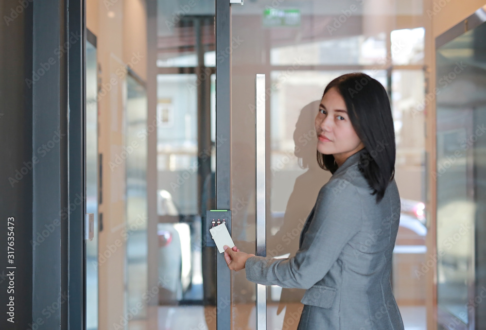 Fototapeta Young officer woman holding a key card to lock and unlock door for access entry. Door access control.