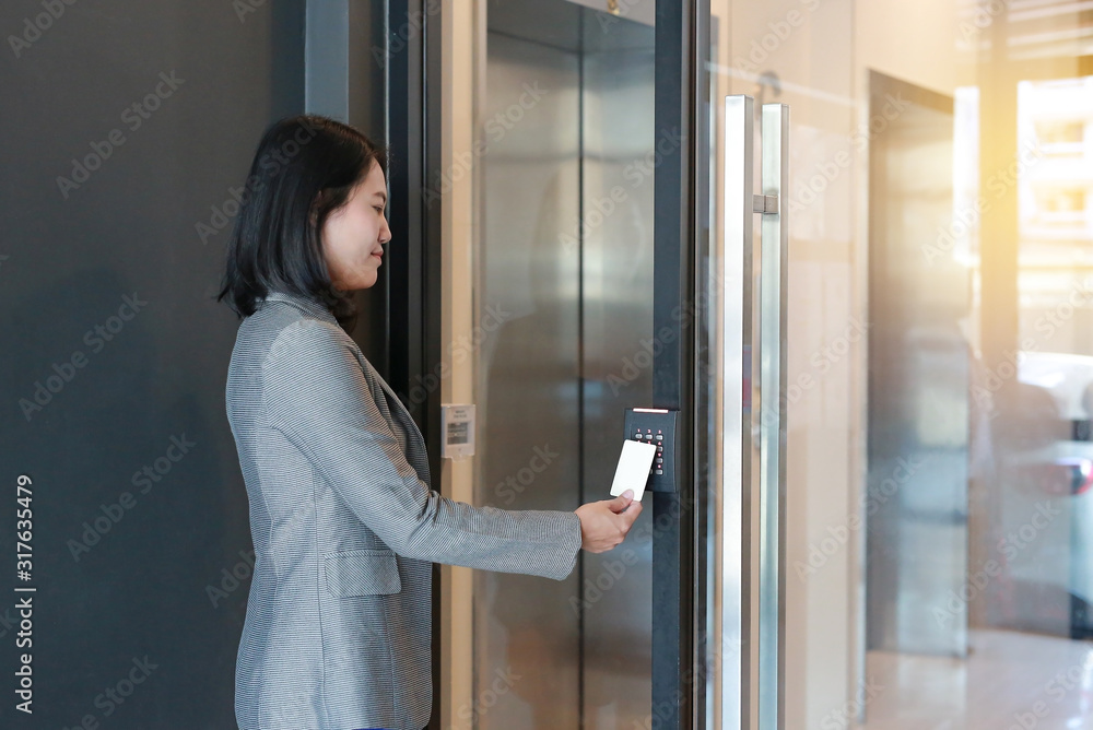 Fototapeta Door access control - young officer woman holding a key card to lock and unlock door for access entry.