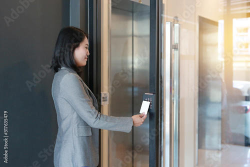 Door access control - young officer woman holding a key card to lock and unlock door for access entry Wallpaper Mural