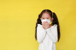 Portrait asian little kid girl sick with wear protective mask and cough gesture isolated over yellow background with copy space.
