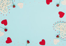 Valentine's Day Blue Background With Rattan And Felt Hearts, Red Roses And Small Red And Pink Hearts. Greeting, Invitation Card. Wedding, Love, Happiness Concept. Flat Lay, Top View With Copy Space.