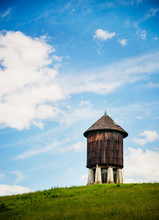 Old Water Tower On A Grassy Hill