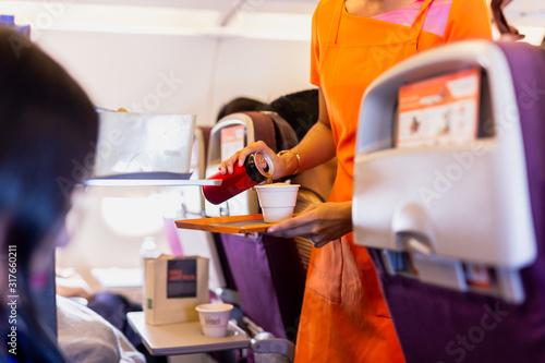 Flight attendant serving drinks to passengers on board. Wallpaper Mural