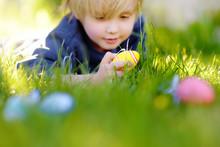 Little Boy Hunting For Easter Egg In Spring Garden On Easter Day. Focus On Multicolor Eggs.
