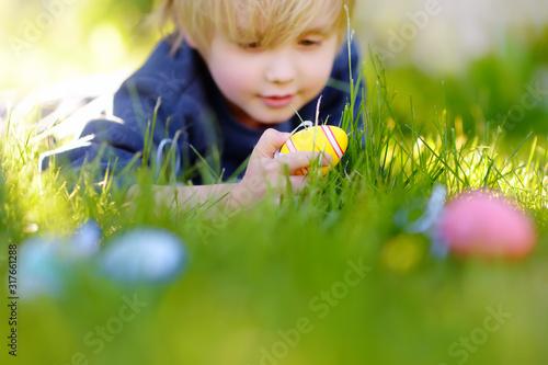 Photo Little boy hunting for easter egg in spring garden on Easter day