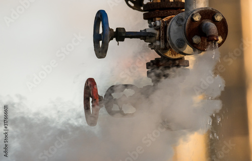 Photo broken valve at the factory hydraulic system, leaking hot liquid and steam under