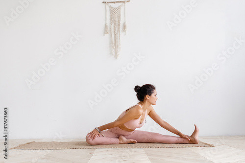 Close-up of a pacified young well-groomed brunette woman doing stretching while doing Pilates exercises sitting on a rug in a pink gymnastic suit on a white background Fototapeta