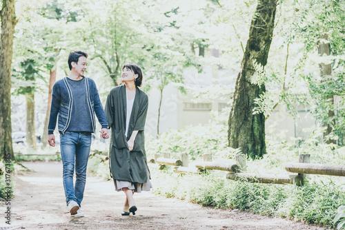 Leinwand Poster 緑の豊かな公園でデートをするカップル