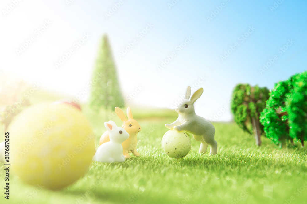 Fototapeta Easter rabbits on green grass with Easter eggs in Dreamland or fairy world.