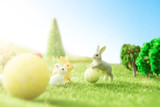 Easter rabbits on green grass with Easter eggs in Dreamland or fairy world.