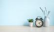 Leinwandbild Motiv Empty blue wall and desk with alarm clock, home plant and ceramic vase. Copy space
