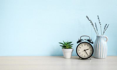 Empty blue wall and desk with alarm clock, home plant and ceramic vase. Copy space