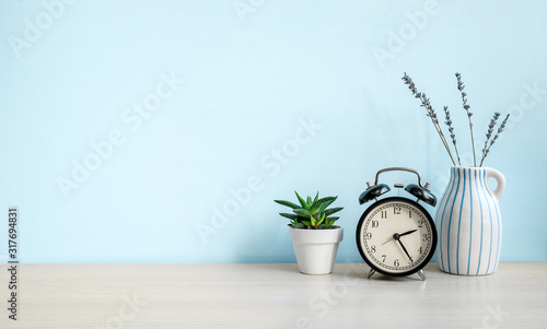 Obraz Empty blue wall and desk with alarm clock, home plant and ceramic vase. Copy space - fototapety do salonu