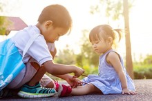 Soft Focus. A Young Asian Brother Help His Little Sister To Tie Her Shoelaces. At The Garden Park In Sunshine Day Summer Season. Love And Family Concept.