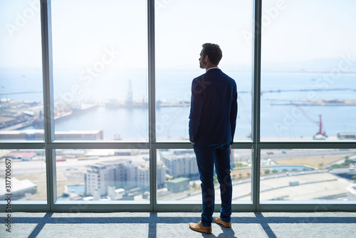 Businessman looking out at harbour through large windows Canvas Print