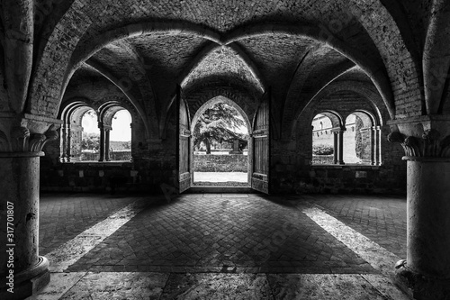Grayscale shot inside of abbey of saint galgano in tuscany italy with arch walls Canvas Print