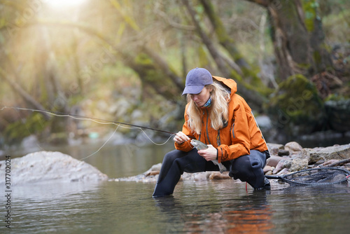 Fototapeta woman fly fishing catching rainbow trout obraz