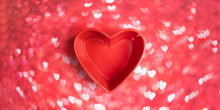 Close-up Three Red Roses In Red Vase Shaped Heart On Pink Bokeh Background With Hearts.