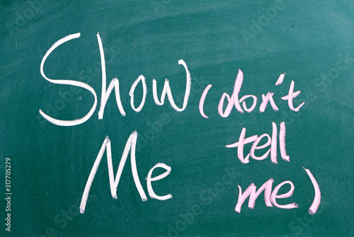 Photo The phrase Show Me, Don't Tell Me written by hand in white chalk on a used blackboard
