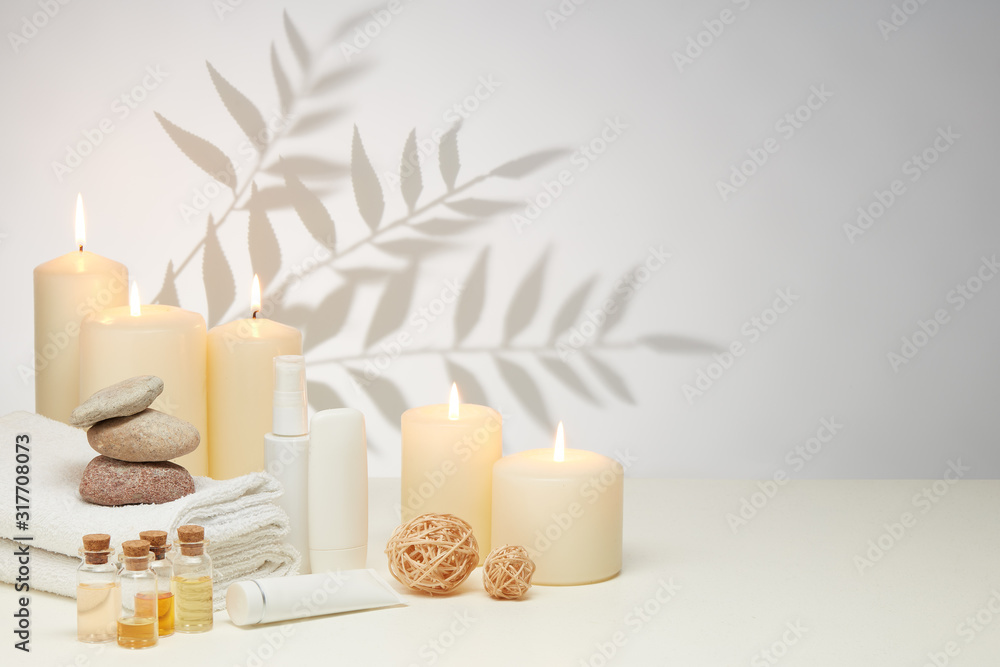 Fototapeta Spa still life with creams, essential oils, candles on light background. Healthy lifestyle, body care, Spa treatment