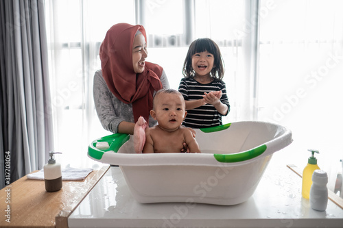 Foto excite baby boy happy taking a bath with muslim mother and sister at home, asian