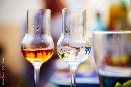 Photo Two grappa glasses with brown and light grappa at a garden party in summer