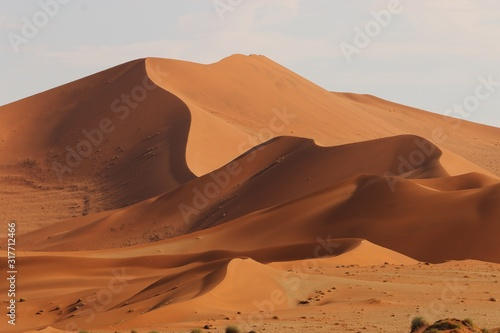 Panoramic shot of beautiful sand dunes with low and high peaks in Namib desert