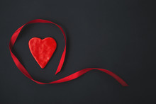 Red Heart With Ribbon Around On Black Background. Valentine's Day Flatlay With Copy Space