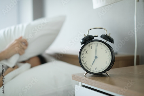 Woman sleep on the bed turns off the alarm clock wake up at the morning, Selective focus Canvas Print