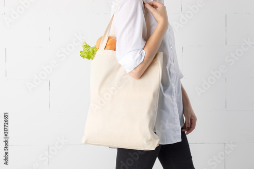 Fototapety, obrazy: Girl is holding cotton eco-bag with green fresh kale and bread.