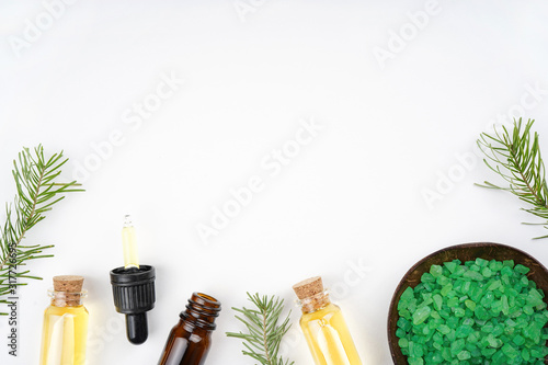 Pine aroma essential oil in bottles, fir branches, bath salt, white background. Spa, beauty, healthcare concept. Top view, flat lay, copy space