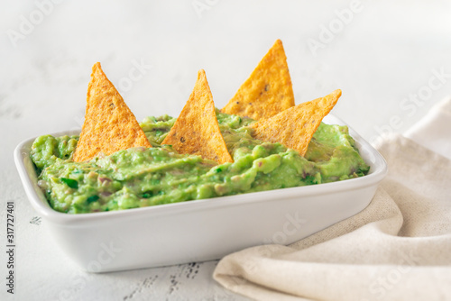 Photo Bowl of guacamole with tortilla chips
