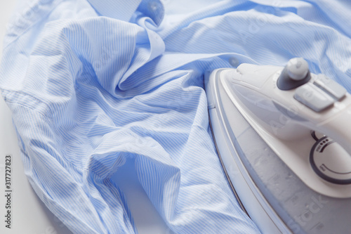 Fotografie, Tablou Blue cotton wrinkled and rumpled shirt ironing with iron