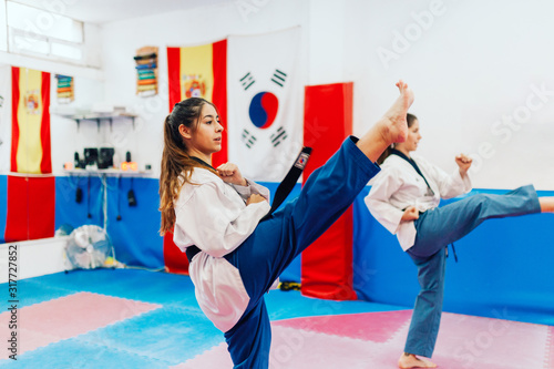 Photo Two young women practice taekwondo in a training center