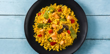 Fried Rice With Chicken And Vegetables In Black Plate On Blue Wooden Table. Top View. Panorama View
