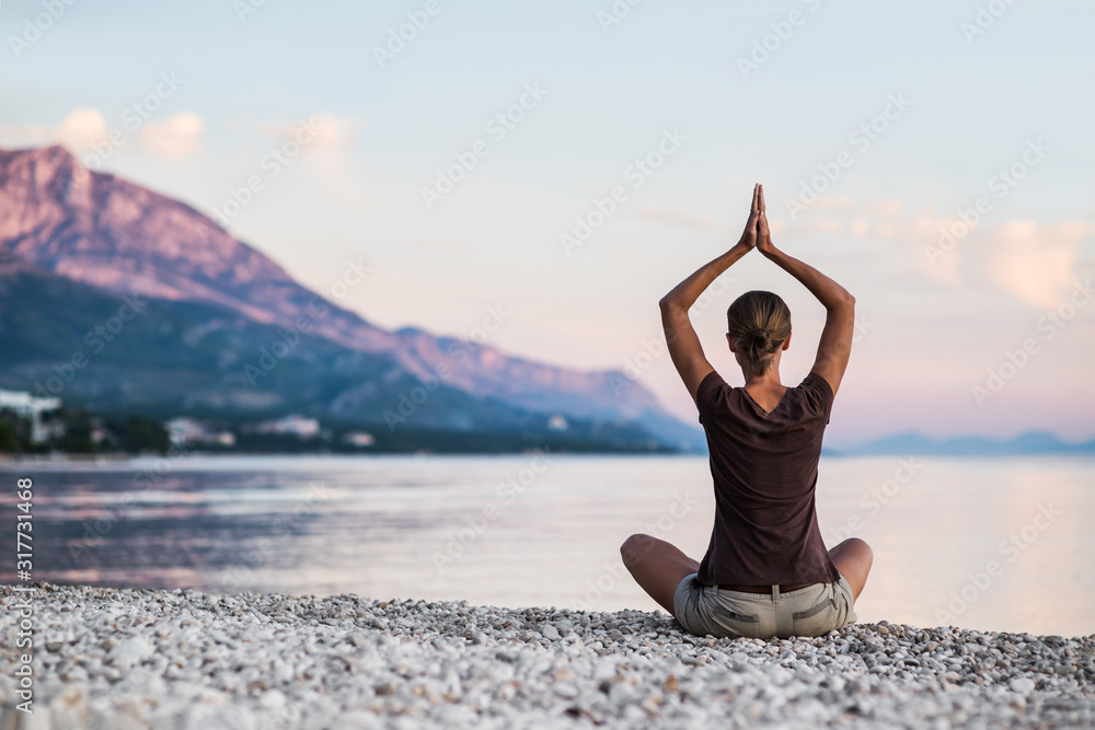 Fototapeta Young woman practicing yoga near the sea. Harmony and meditation concept. Healthy lifestyle