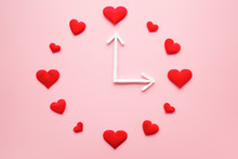 Clock Created From Bright Red Hearts And White Arrows On Light Pink Table Background. Dating Time. Love Concept. Closeup. Flat Lay.
