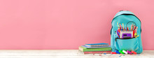 Banner Full Turquoise School Backpack With Stationery On Table On Pink Background. Back To School Concept.