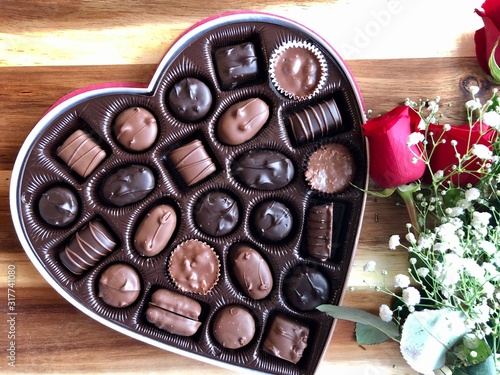 heart shaped box of valentine's day chocolates and a bouquet of red roses on a wooden table