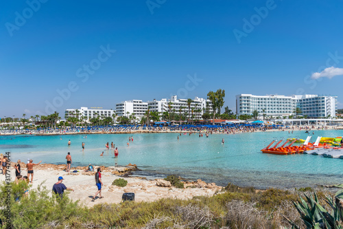 CYPRUS, NISSI BEACH - MAY 12/2018: Tourists relax and swim on one of the most popular beaches on the island Wallpaper Mural