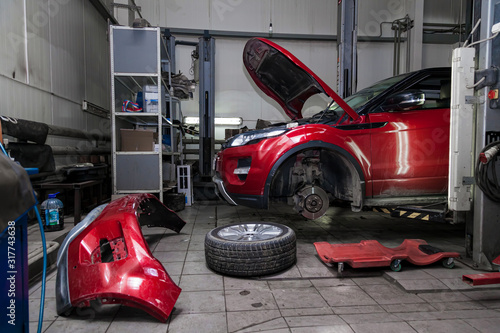 Cuadros en Lienzo Red used car with an open hood raised on a lift for repairing the chassis and engine with removed wheels and broken bumper in a vehicle repair shop