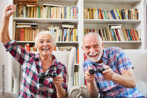 Photo Paar Senioren spielt Videospiel mit Konsole im Wohnzimmer
