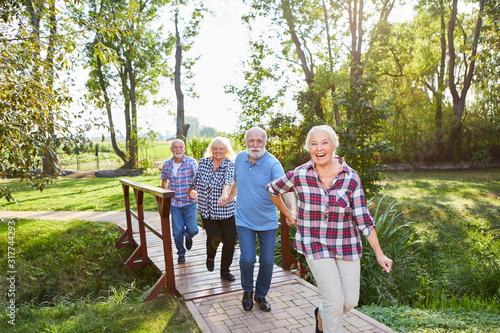 Obraz Senioren laufen fröhlich auf einem Wanderweg - fototapety do salonu