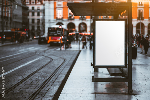 Obraz A blank advertising billboard placeholder template on the city street; an empty mock-up of an outdoor poster on a paved tram stop; a white vertical mockup of an urban banner on the bus stop - fototapety do salonu