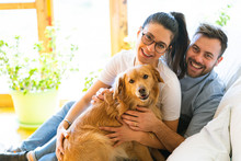 Happy Couple With A Golden Retriever Dog Sitting On A Sofa Smiling And Positive